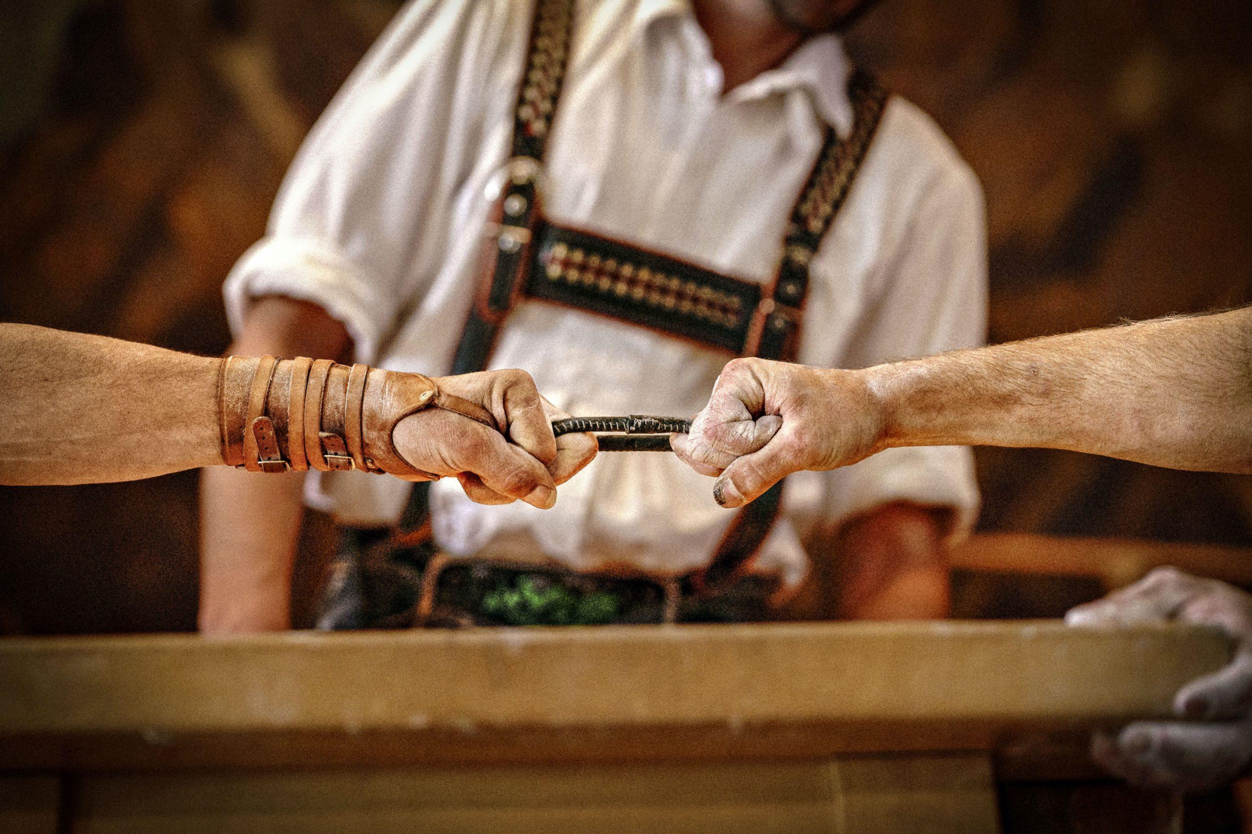 Zwei kräftige Hände von Fingerhaklern ziehen an einem Lederriemen