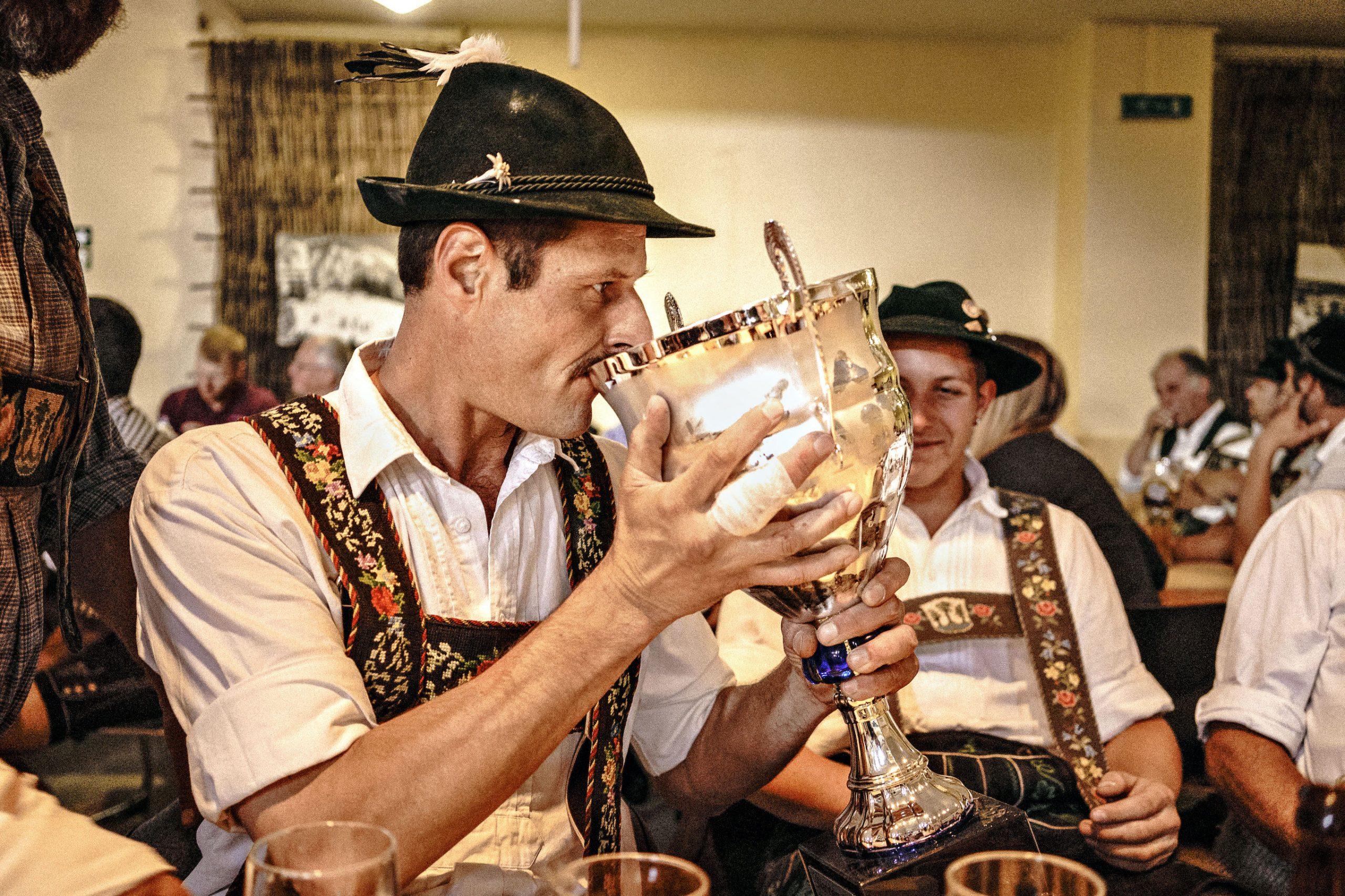Ein Fingerhakler in Tracht trinkt aus einem Pokal.