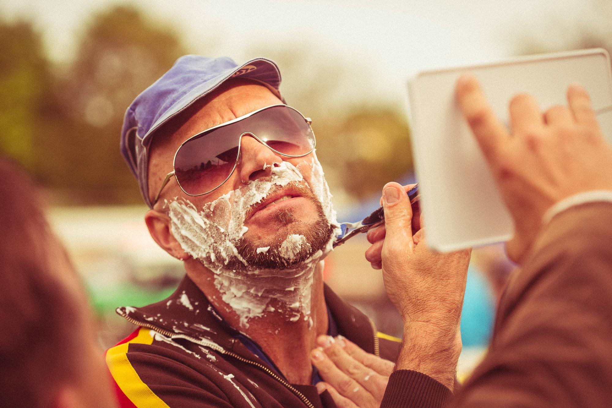 Ein Teilnehmer der Klapprad-WM hat Rasierschaum im Gesicht und rasiert sich vor dem Start.