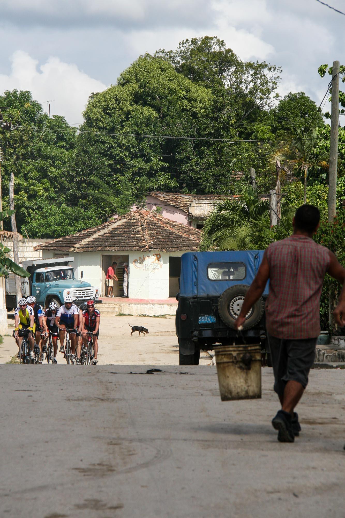 Ein Mann trägt einen Eimer durch eine Straße. Auf ihn fährt eine Gruppe Rennradfahrer zu.