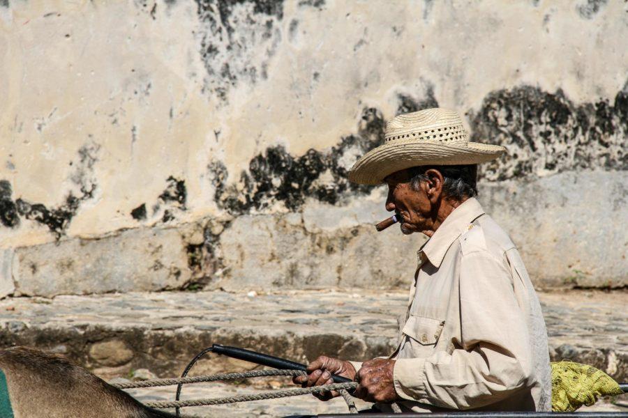 Ein alter zigarrenrauchender Mann reitet durch Trinidad.