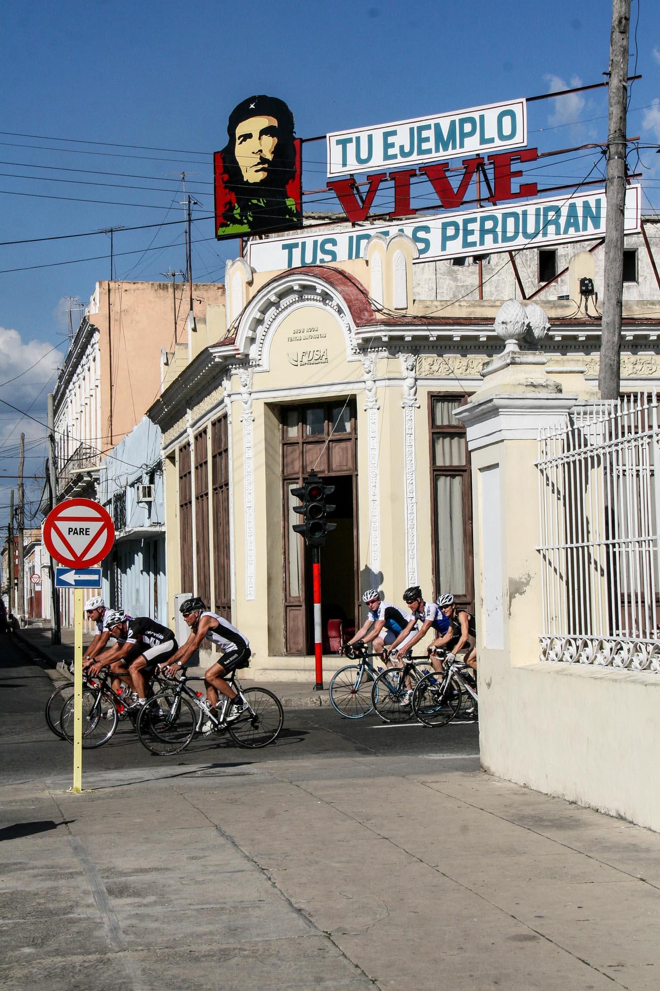 Eine Gruppe Rennradfahrer fährt vor einem Haus mit einer Che-Guevara-Beschriftung.