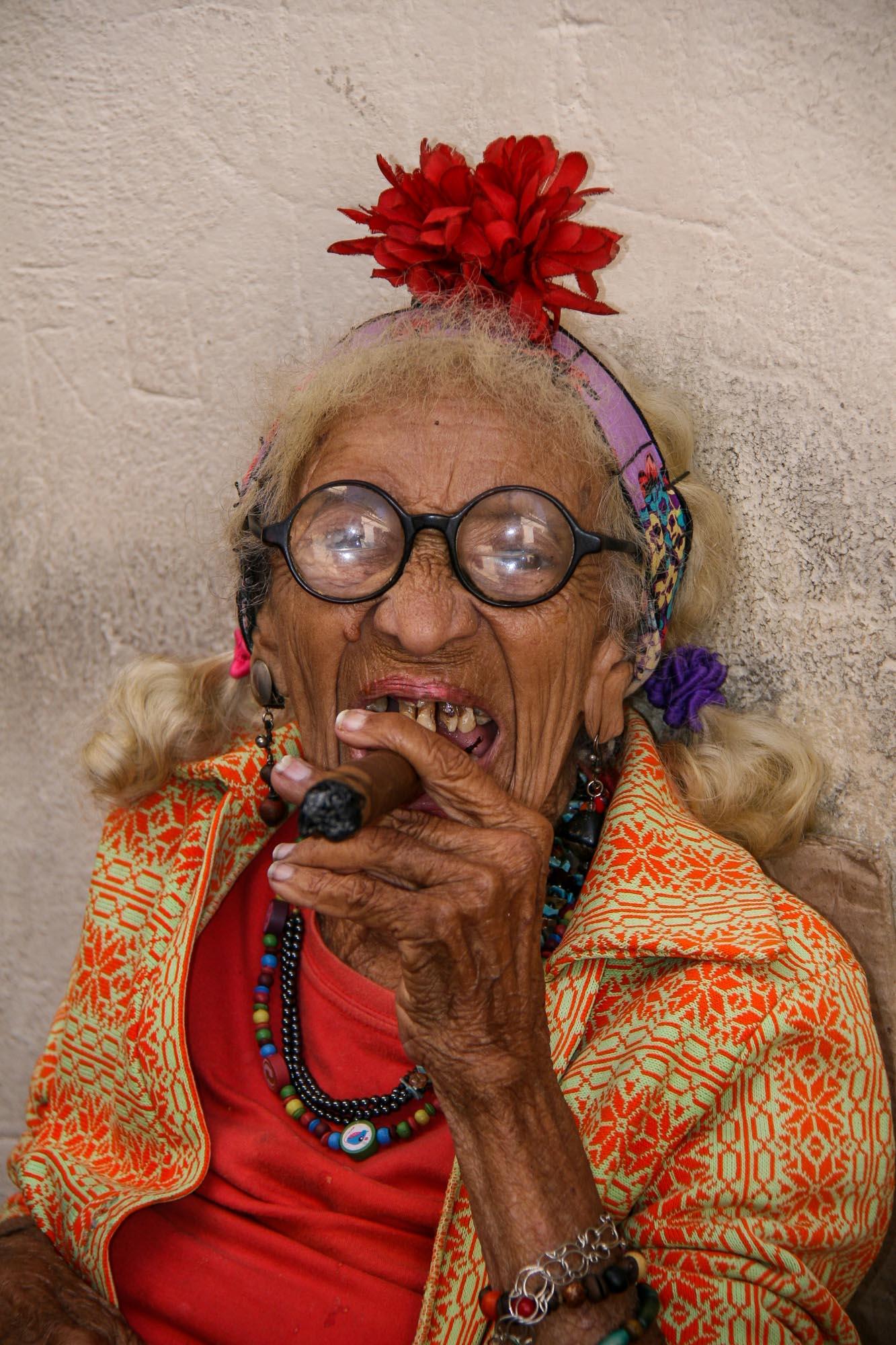 Eine alte Frau raucht eine Zigarre.
