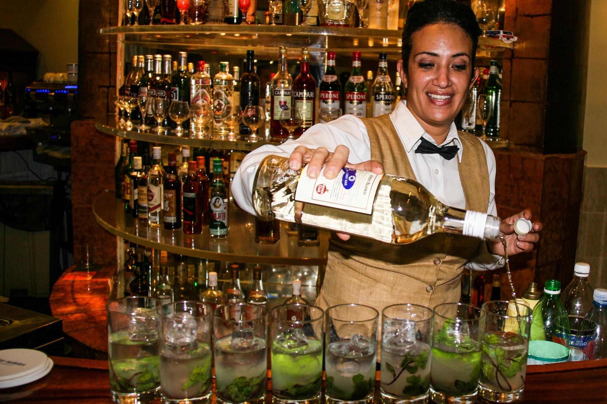 Eine Barkeepern schenkt Rum in acht Gläser ein.