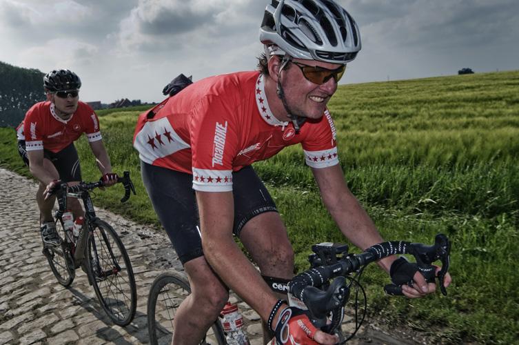 Zwei Rennradfahrer fahren auf einem Kopfsteinpflasterstück