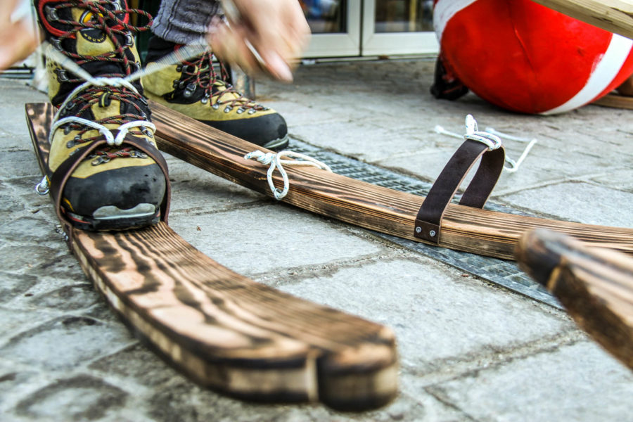 Schuhe werden auf historische Holzski geschnürt
