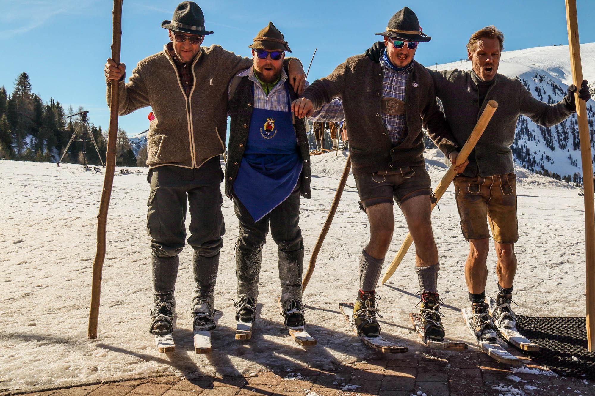 Vier Männer fahren Arm in Arm in Tracht auf historischen Ski