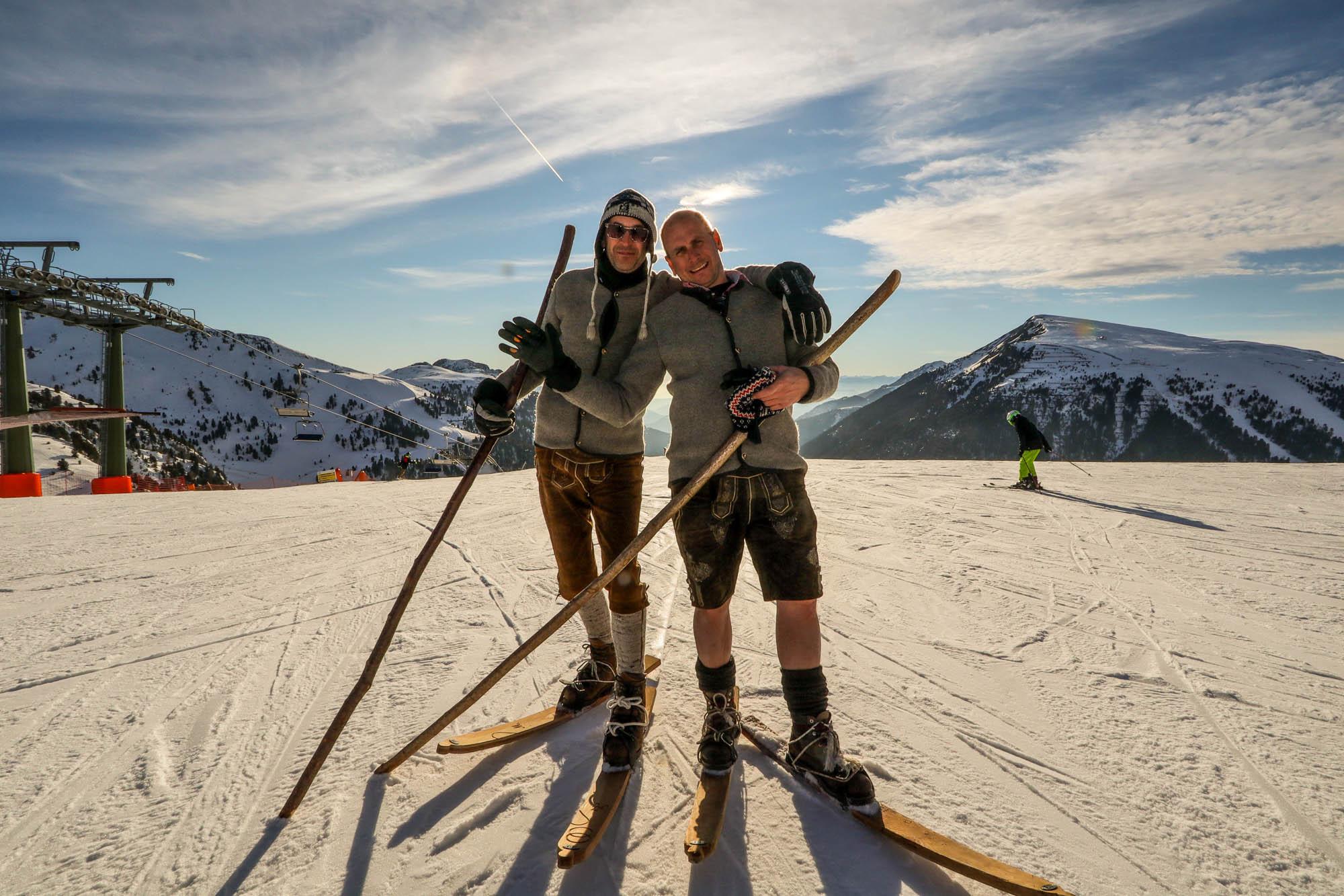 Zwei Männer in Tracht stehen vor dem Panorama in Obereggen auf historischen Ski