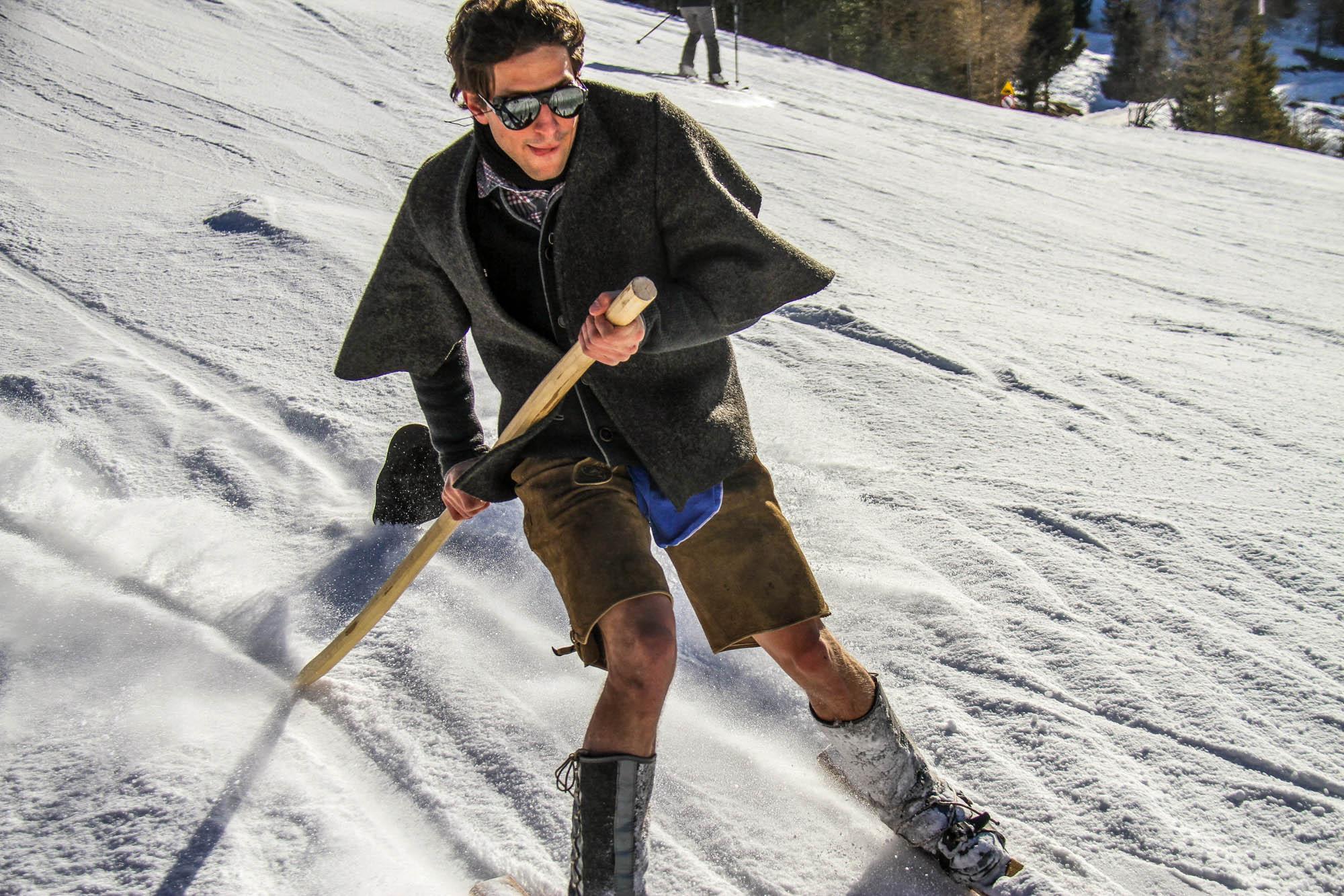 Ein Mann fährt auf der Skipiste mit historischen Holzski