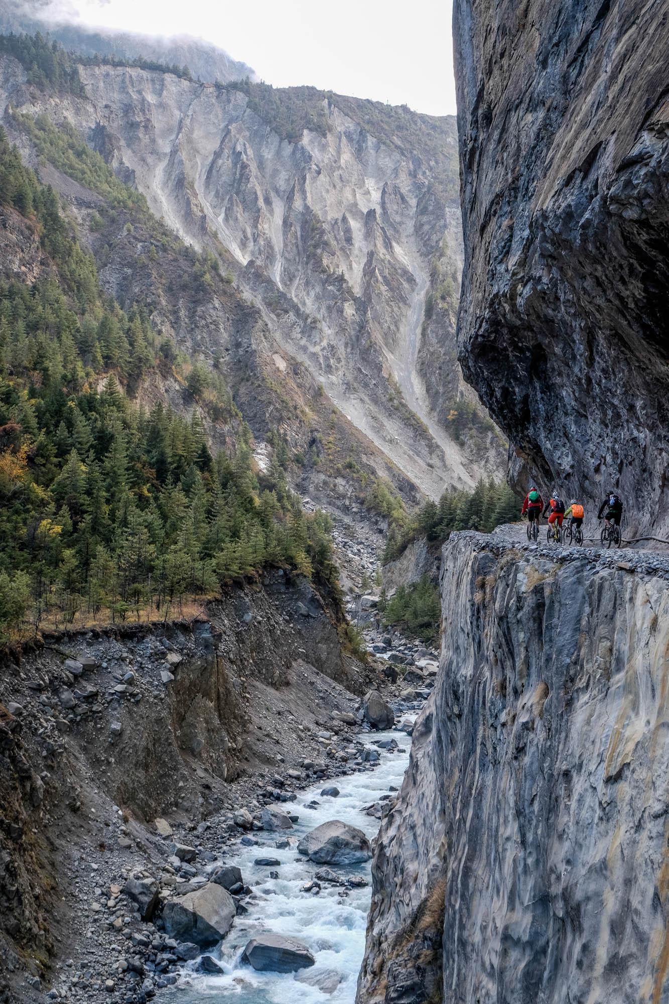 Vier Mountainbiker fahren auf einem Weg an einem senkrechten Abgrund