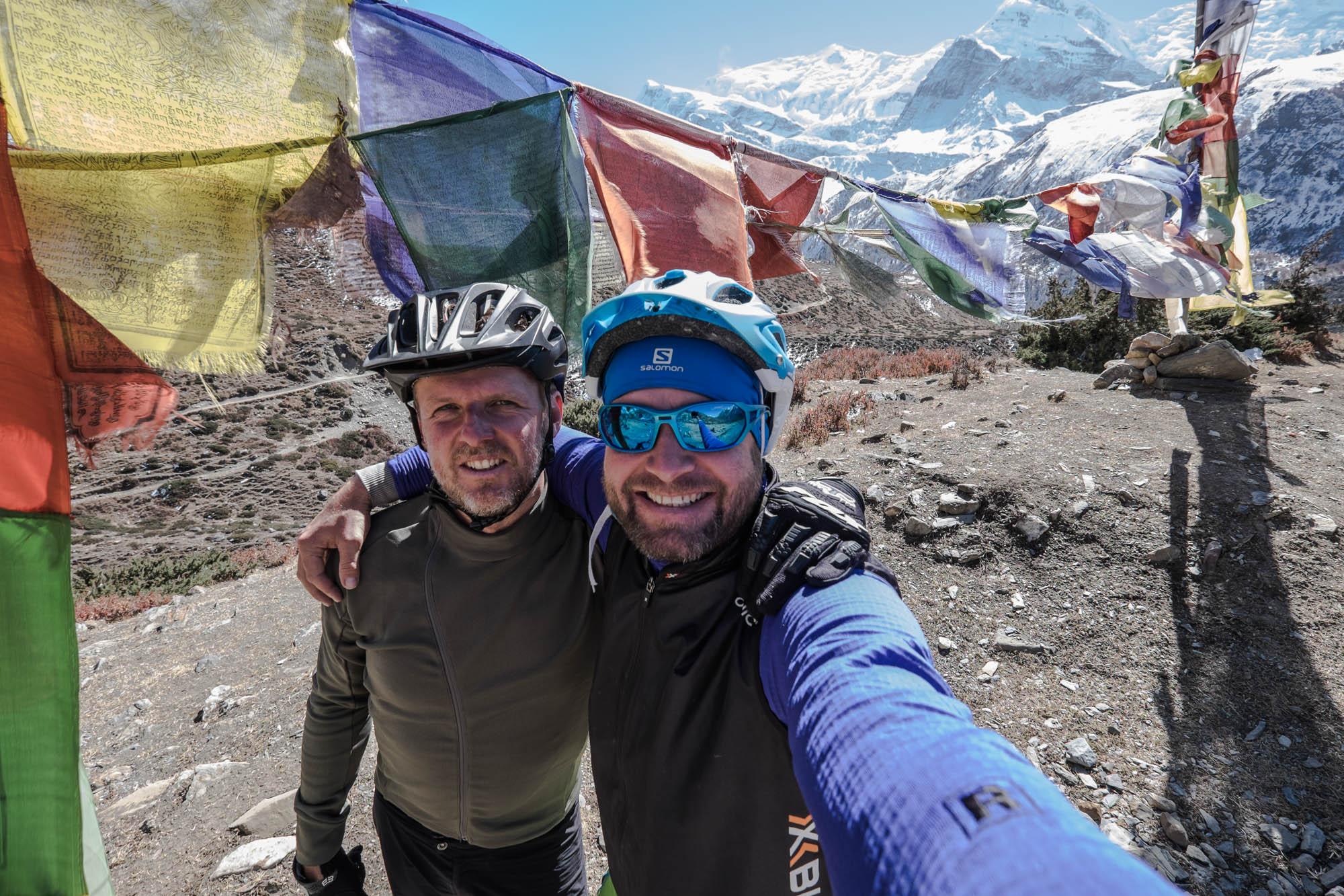 Selfie von Jens Vögele und Andreas Kern neben buddhistischen Gebesfahnen und vor dem Panorama des Himalaja.
