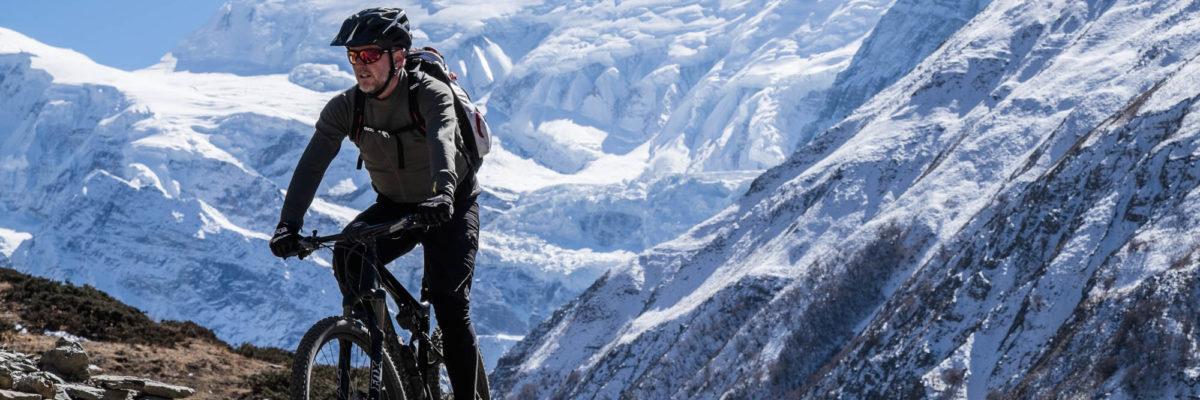 Ein Mountainbiker fährt vor einem vereisten Himalaja-Massiv