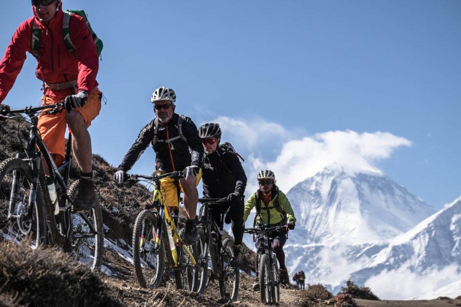 Vier Mountainbiker fahren einen Wanderpfad vor einem Himalaja-Gipfel rauf