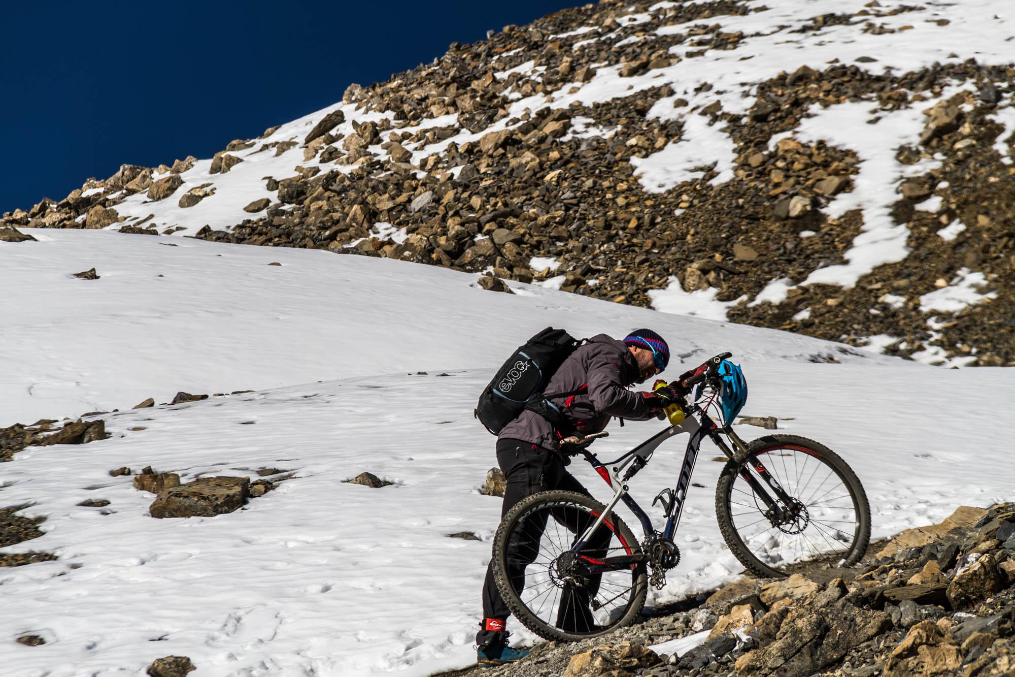 Ein Mountainbiker schiebt erschöpft sein Rad neben einem Schneefeld