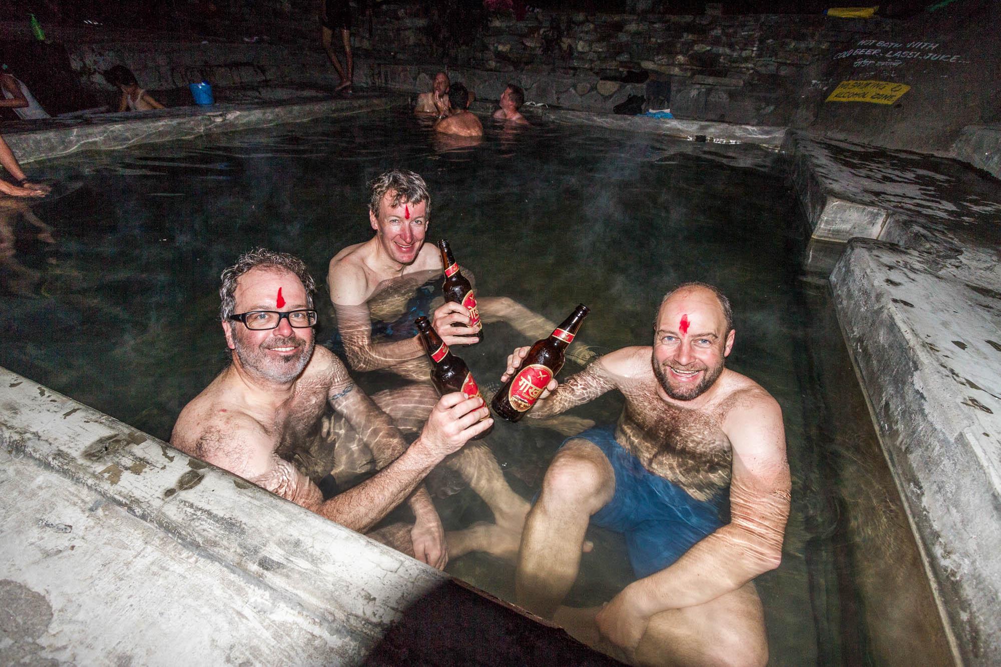 Drei Männer nehmen ein Bad in einer warmen Quelle