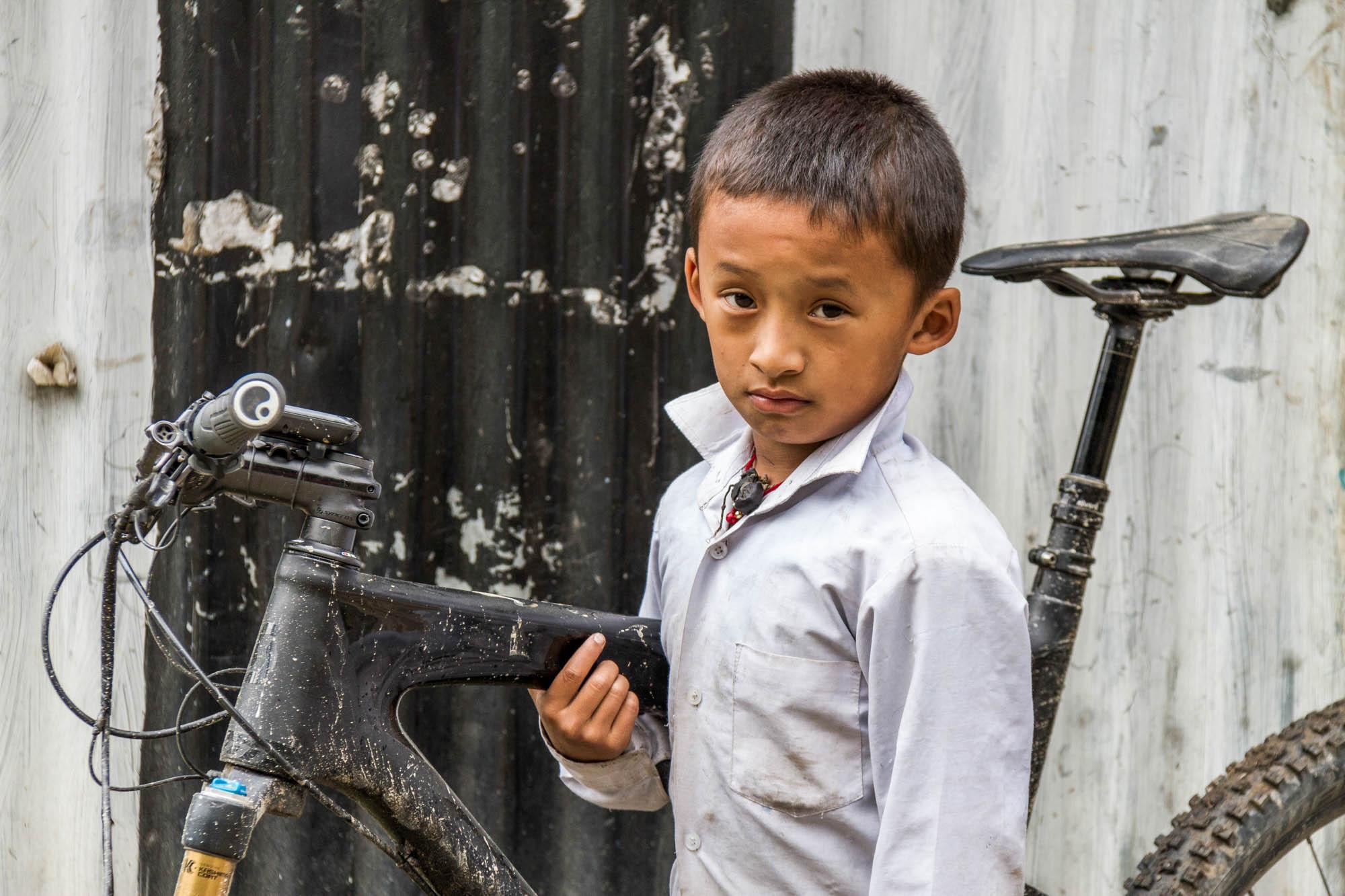 Ein nepalesischer Junge hält ein Mountainbike
