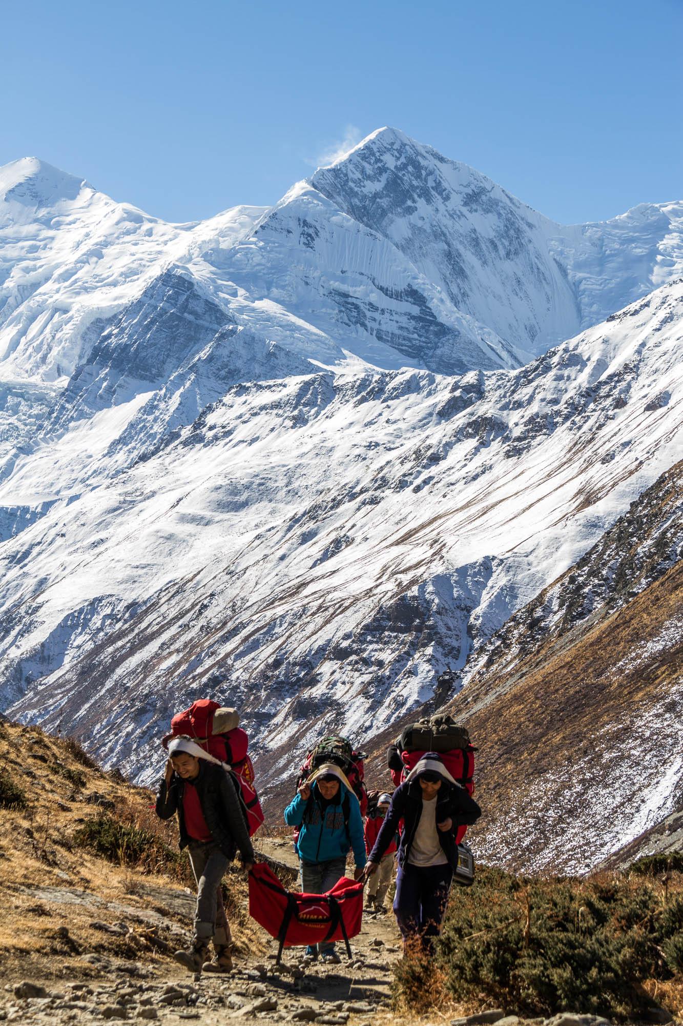 Drei Männer tragen schweres Gepäck den Berg hoch