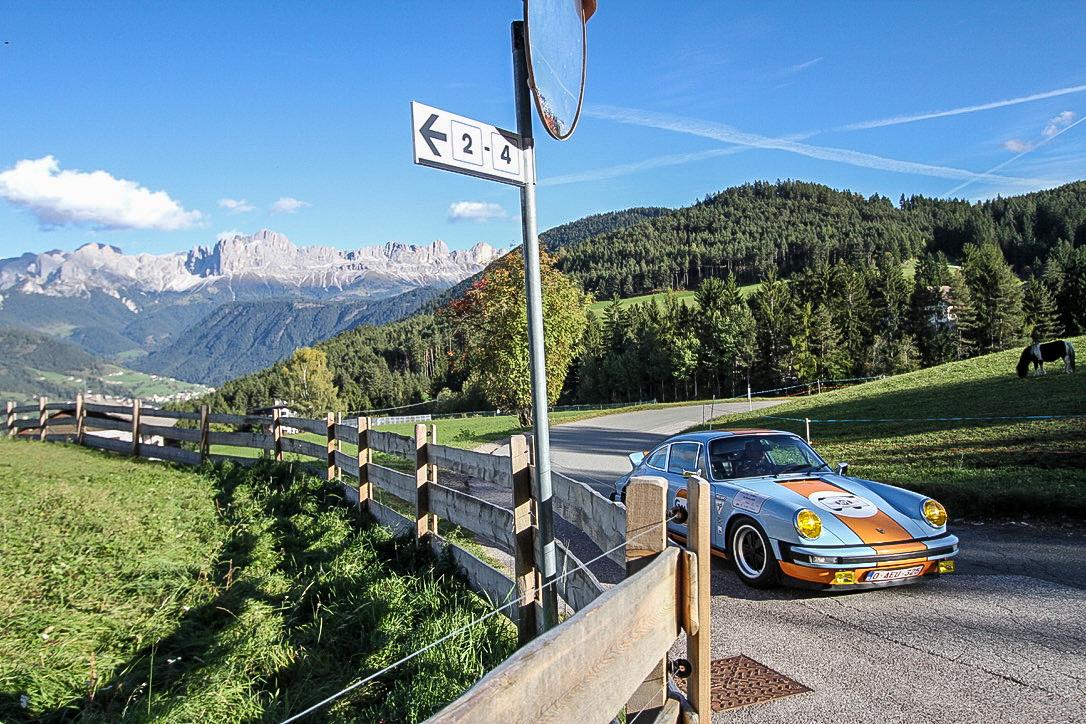Ein Porsche fährt vor dem Panorama des Rosengartens.