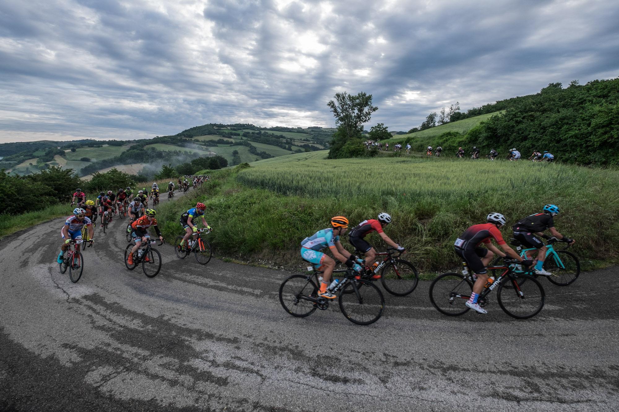 Eine Gruppe von Rennradfahrern fährt eine Serpentine hoch