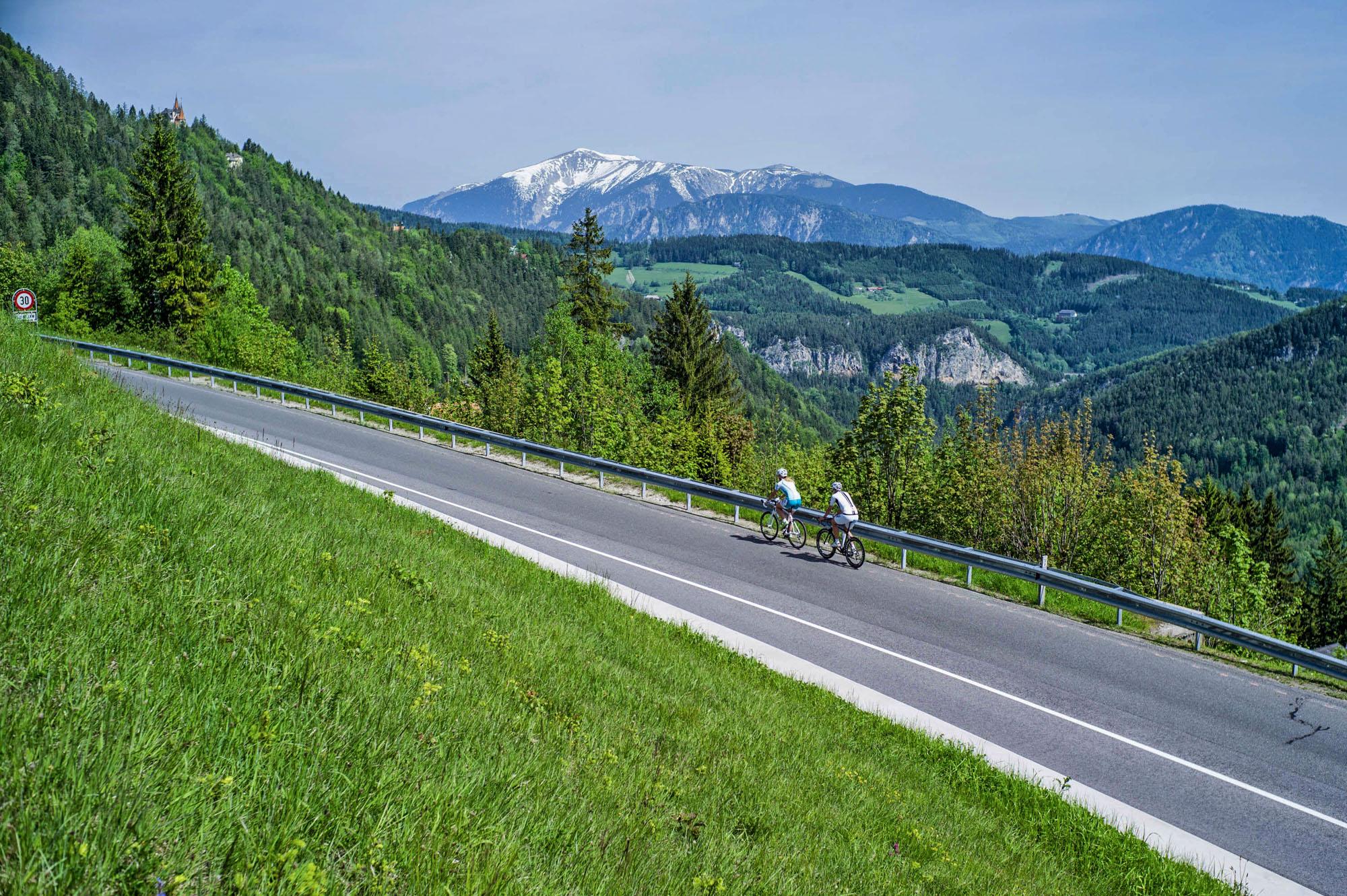 Zwei Radfahrer vor dem Panorama des Schneebergs