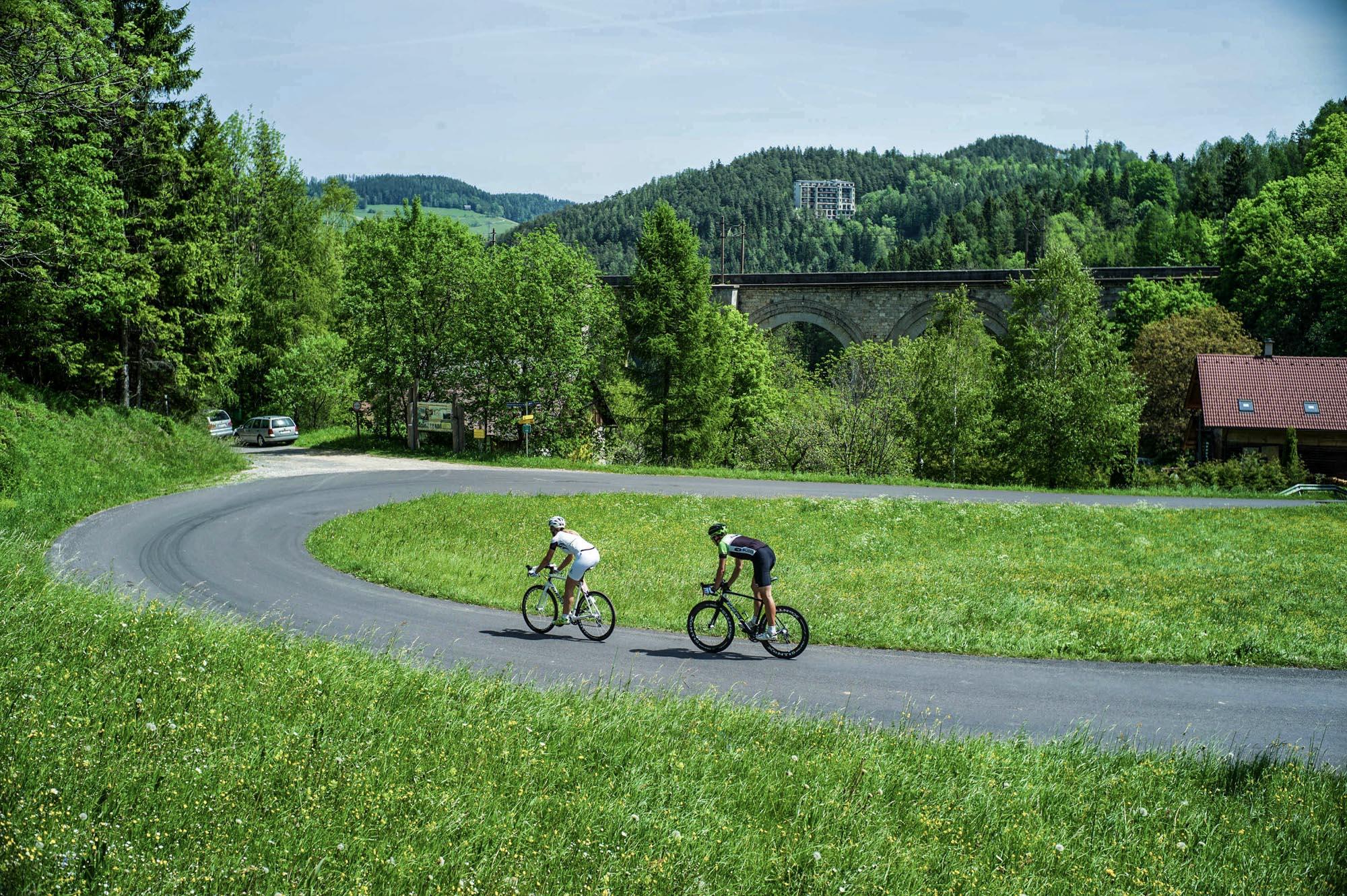 Zwei Radfahrer fahren auf das Viadukt der Semmeringbahn zu