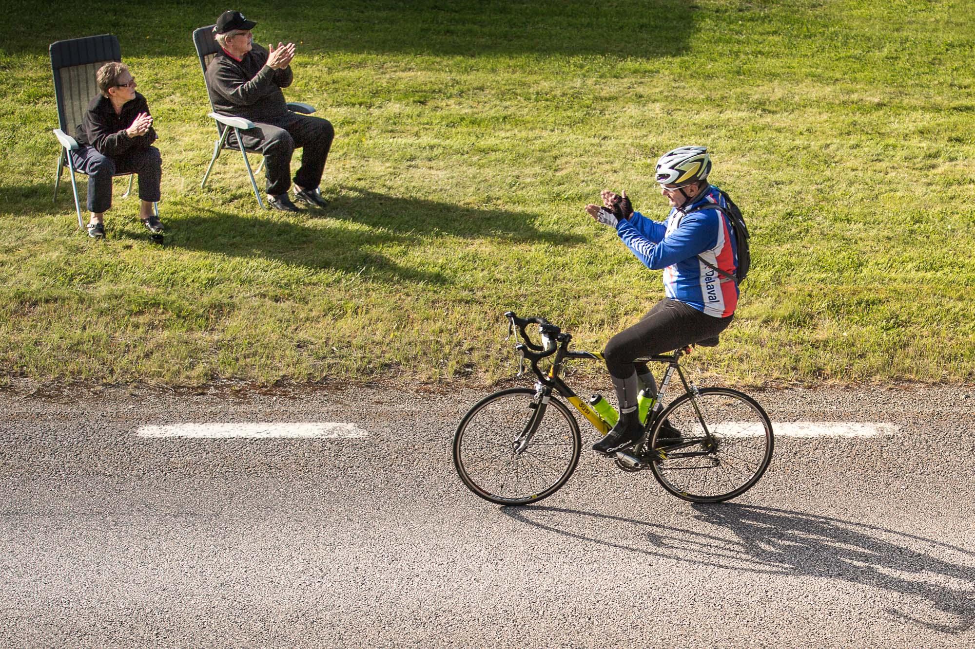 Ein Radfahrer bedankt sich bei klatschenden Zuschauern