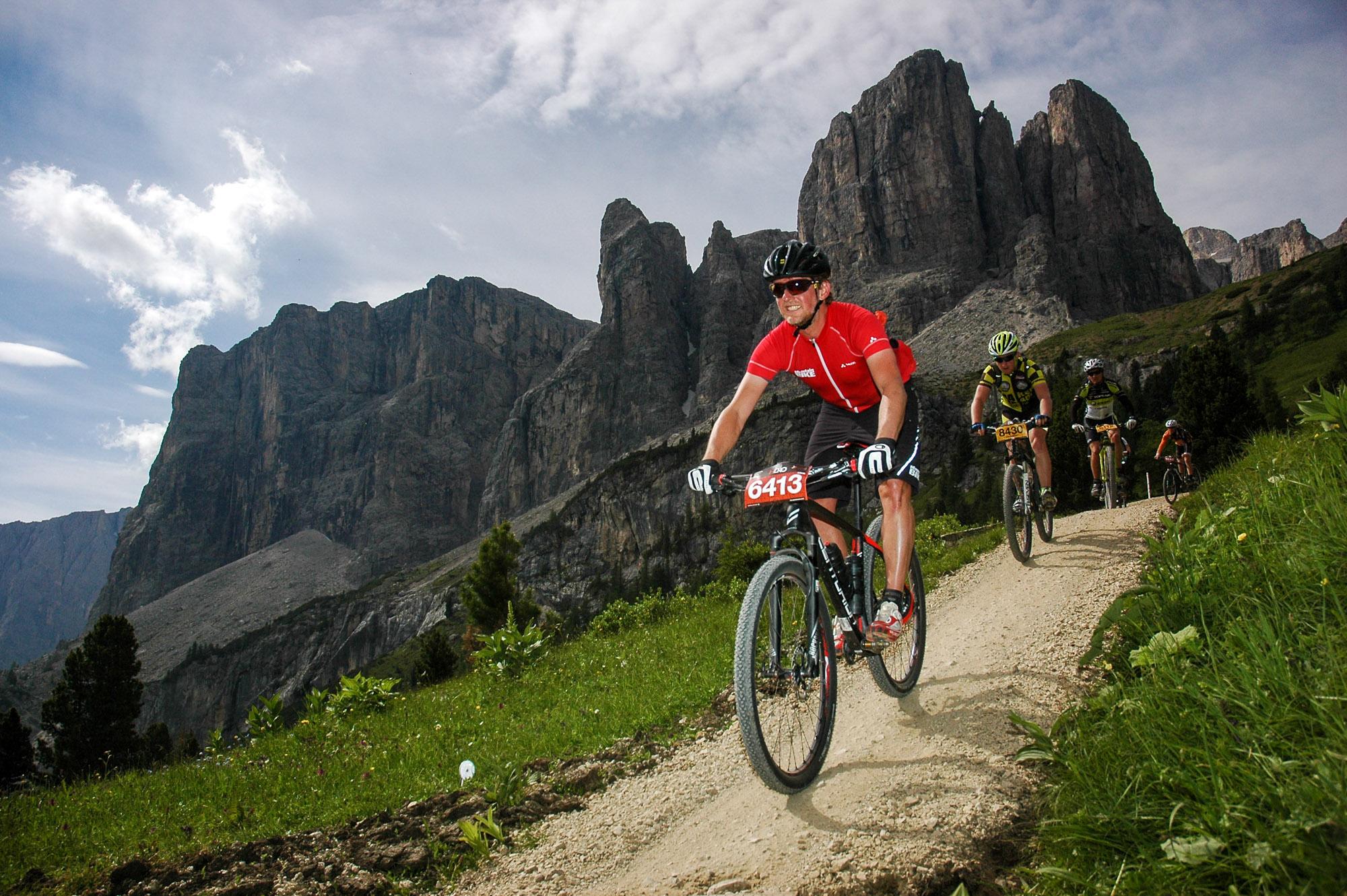 Ich fahre mit einer Gruppe von Mountainbikern vor dem Dolomitenpanorama.