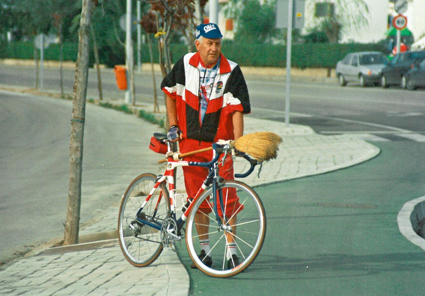Ein Mann steht mit einem Besen hinter seinem Fahrrad