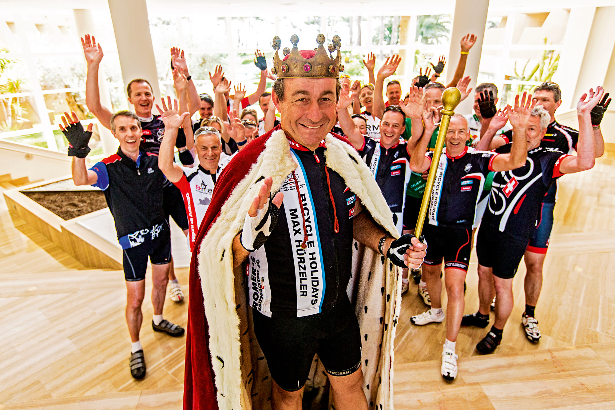 Max Hürzeler steht im Königsgewand vor einer Gruppe Radfahrern
