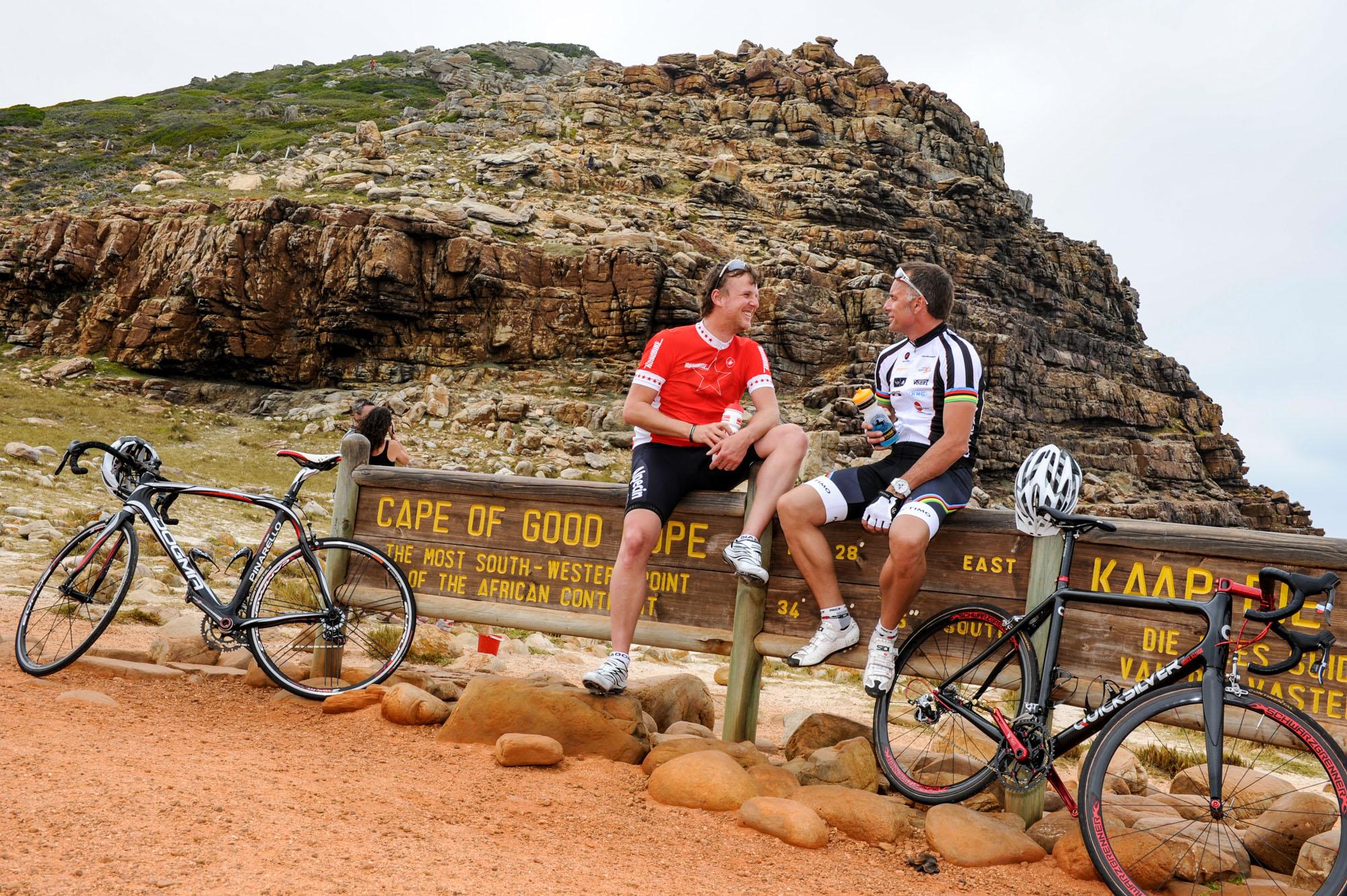 Jens Vögele und Mike Kluge sitzen auf dem Schild am Kap der Guten Hoffnung