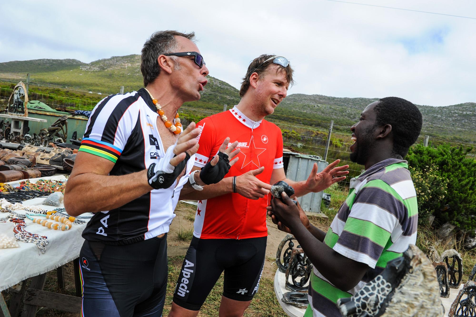 Jens Vögele und Mike Kluge verhandeln mit einem Marktverkäufer.