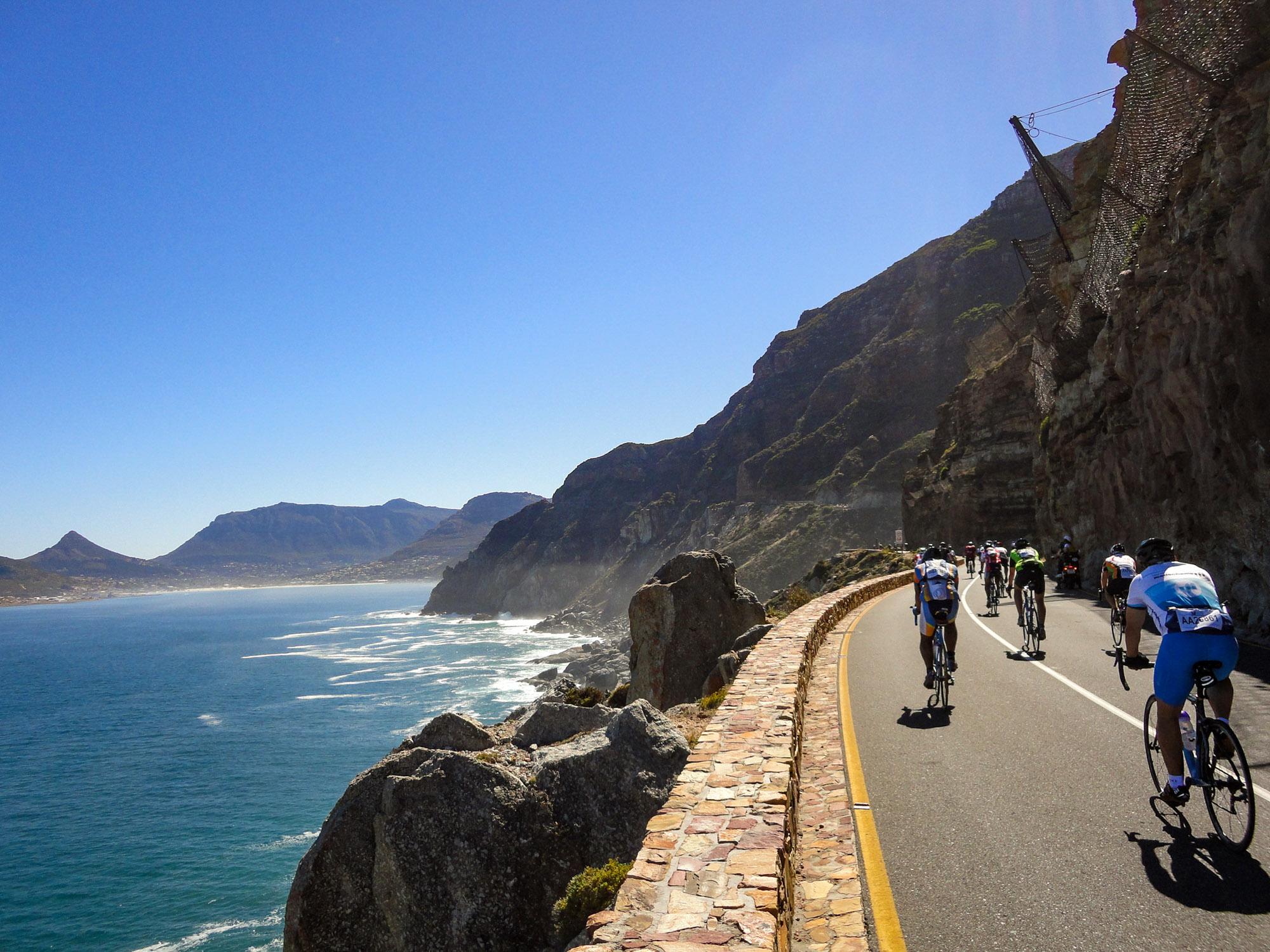 Beim Cape Argus: Rennradfahrer fahren auf einer Küstenstraße