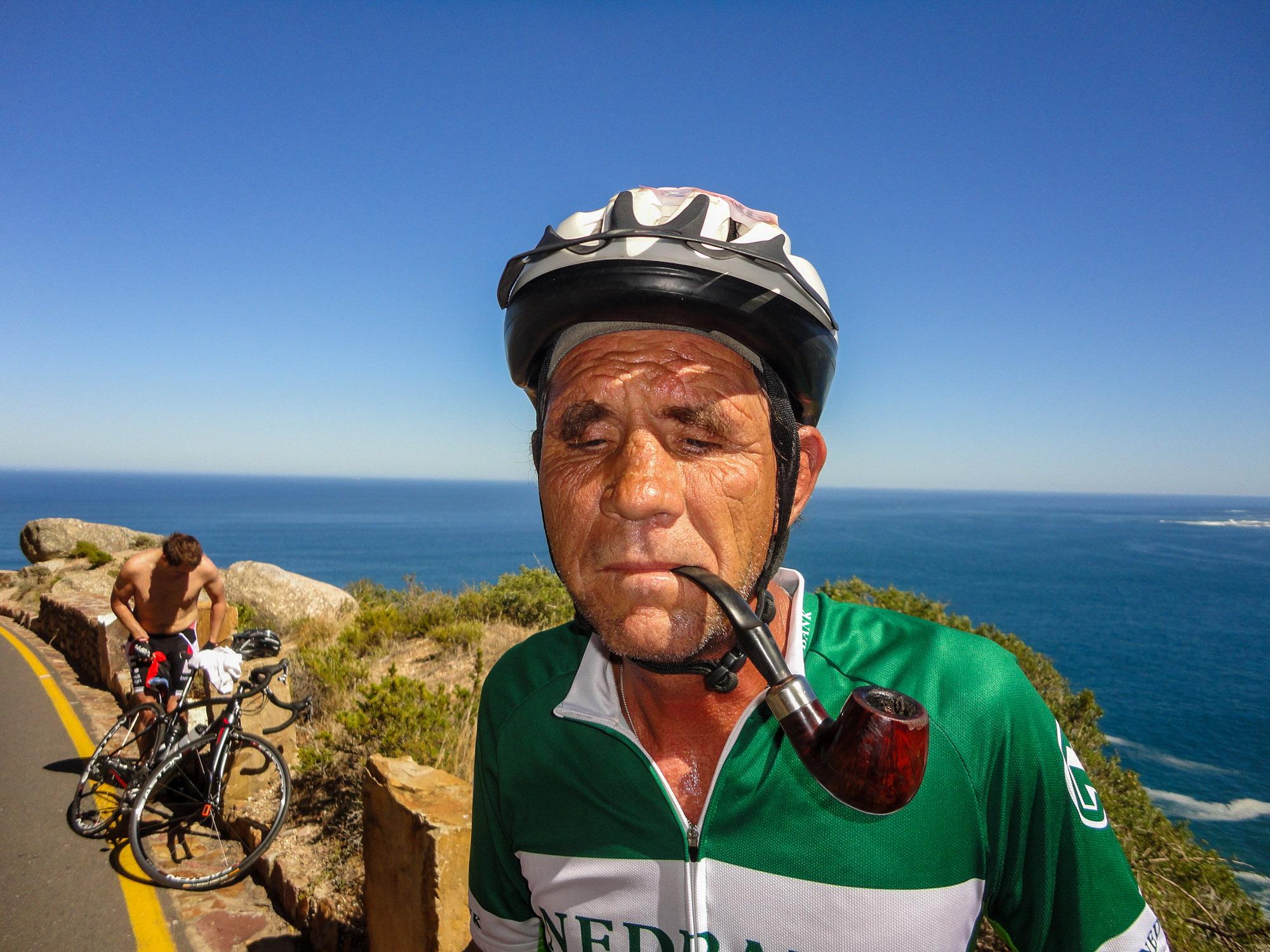Ein Fahrradfahrer macht eine Pause und raucht dabei eine Pfeife