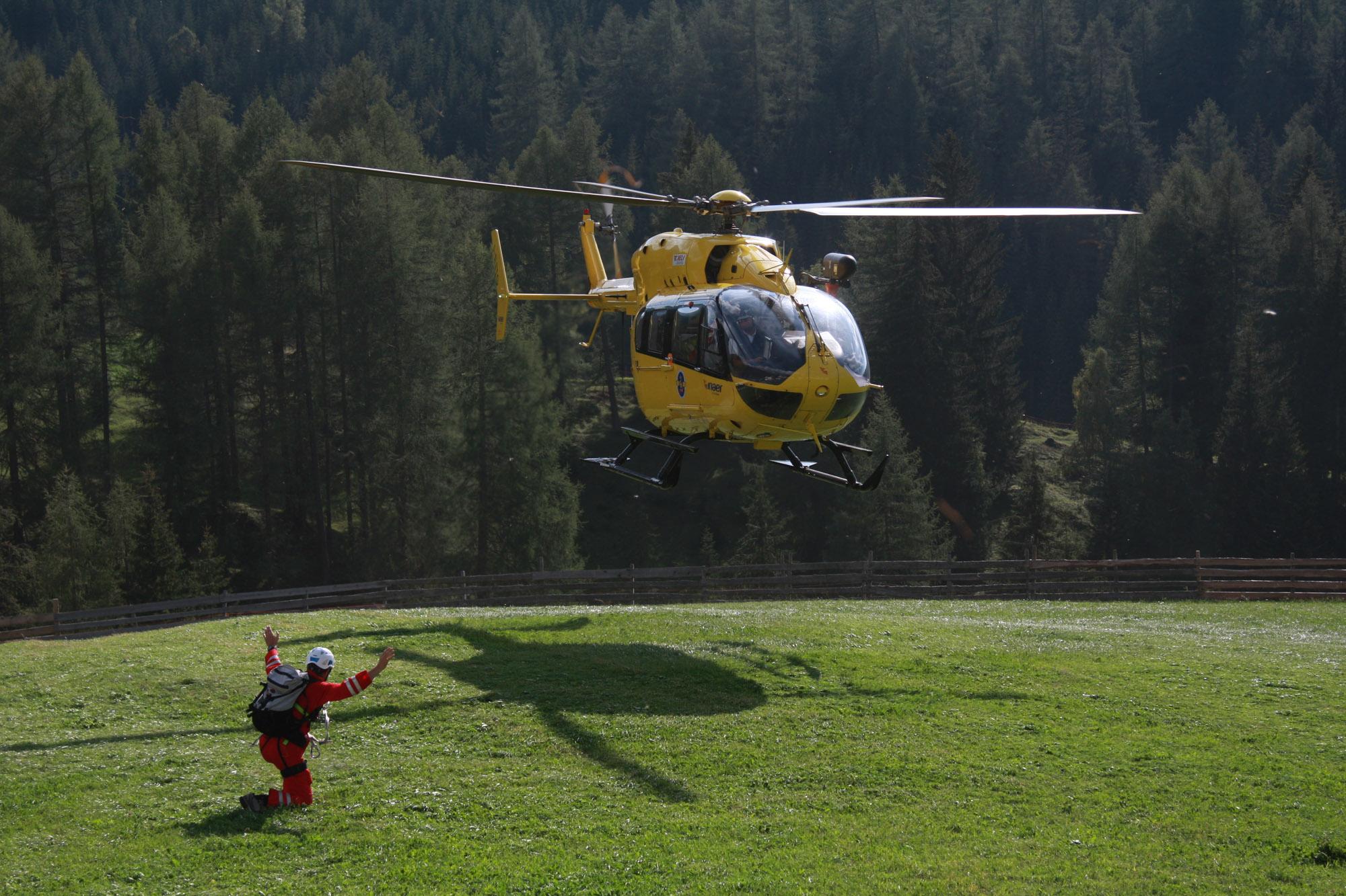 Ein Hubschrauber der Bergrettung landet auf einer Wiese