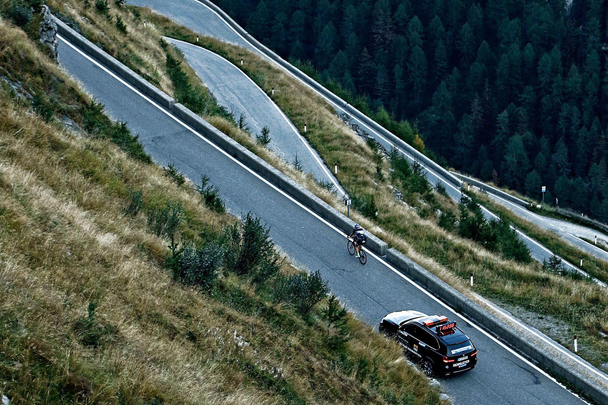 Ein Radfahrer fährt gefolgt vom Besenwagen die Serpentinen des Timmelsjoch hoch
