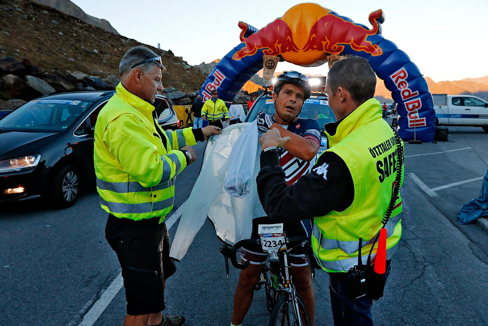 Ein entkräfteter Radfahrer zieht sich eine Jacke an