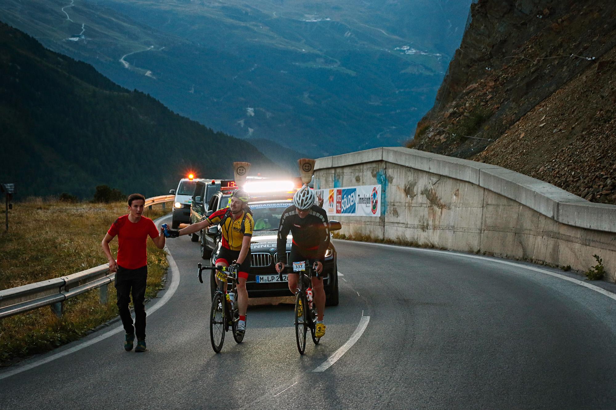 Zwei Radfahrer kämpfen sich den Berg hoch, dicht gefolgt vom Besenwagen