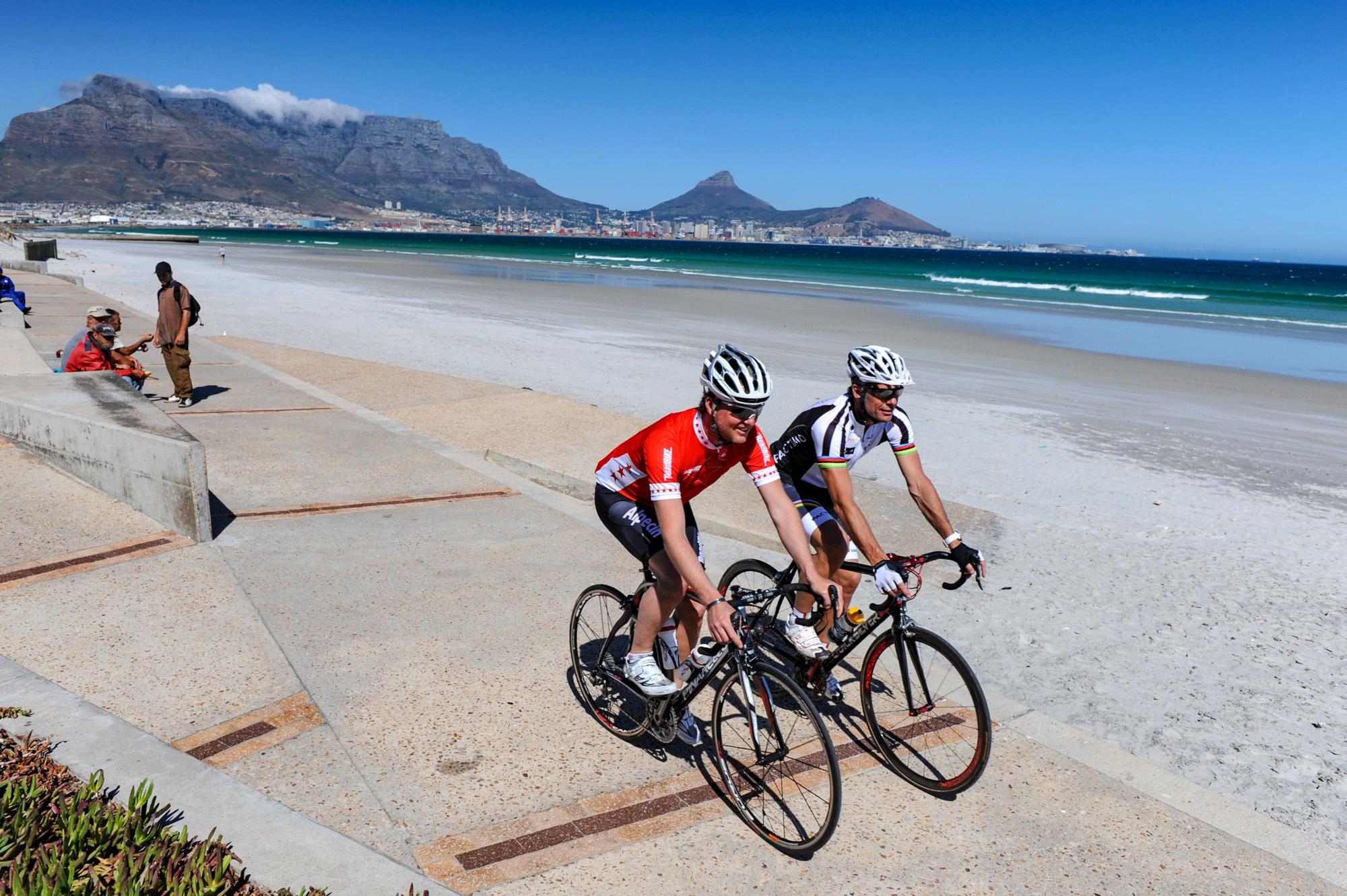 Jens Vögele und Mike Kluge fahren mit ihren Rädern in Kapstadt mit dem Tafelberg im Rücken