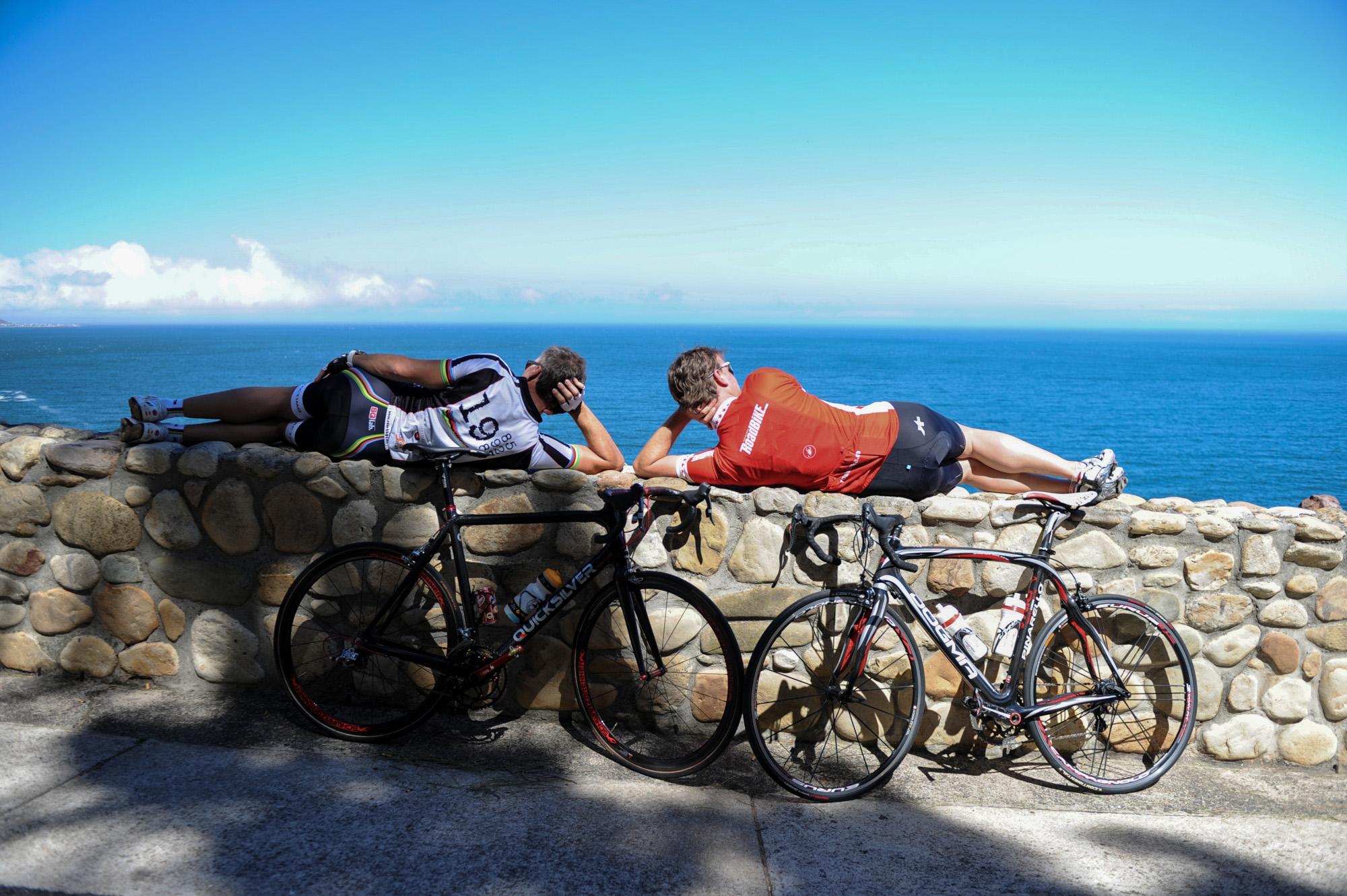 Jens Vögele und Mike Kluge liegen auf einer Mauer und blicken aufs Meer