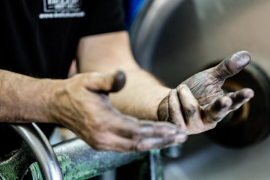 Schmutzige Hände zeigen die schwere Arbeit in der Manufaktur Bolichwerke.