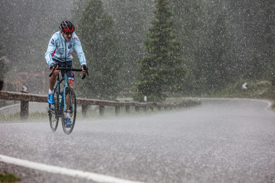 Extremsportler Guido Kunze fährt mit seinem Rennrad auf einem Pass der Sella Ronda durch heftigen Regen
